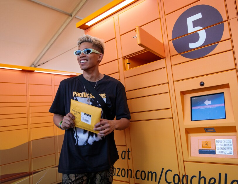 A man stands next to an open locker at at Amazon Lockers installation. He wears sunglasses and holds a package.