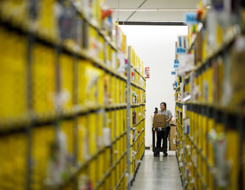 A person stands in the distance at the end of facing rows of yellow shelves at a Prime Now facility in Seattle, Washington.