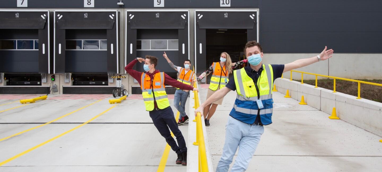 4 Mitarbeiter:innen mit Masken steht vor einem Logistikgebäude.