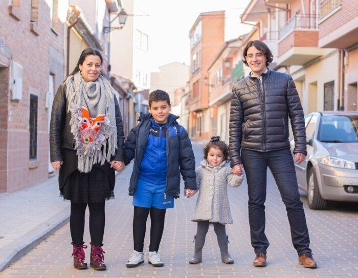 Carmelo Castro en una calle de Pozoantiguo, Zamora, acompañado de su esposa y sus dos hijos. Él viste casual yella con un vestido negro y un pañuelo gris y naranja. Él hijo va vestido para ir a entrenar a fútbol y la hija con unos leotardos y una chaqueta gris.