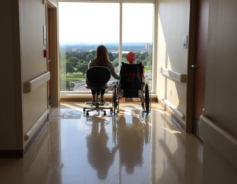 Photographed from behind, a woman in a chair holds hands with a teen in a wheelchair. They look out a windown toward the horizon.