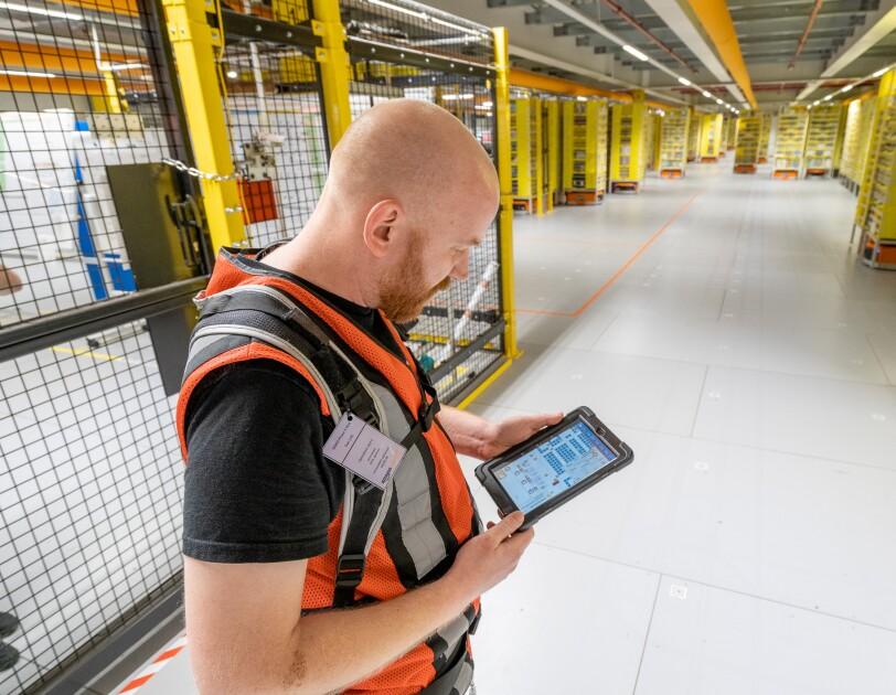 Ein Mitarbeiter mit Sicherheitsweste und Tablet steht in einem Bereich mit Transportrobotern.