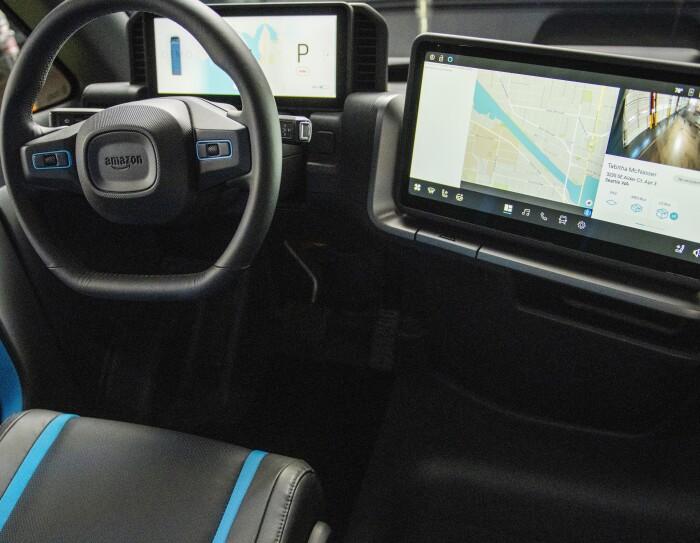 Primer plano del volante y de la pantalla de navegación. A la derecha el volante de color negro con el logo de Amazon y una pantalla con la información técnica relacionada con el coche. A la derecha una pantalla de navegación con un mapa y una fotografía del destino.