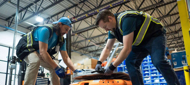 Dwaj mężczyźni w przestrzeni magazynowej sięgają w dół, by zabezpieczyć srebrny przedmiot na pomarańczowej, kołowej maszynie.