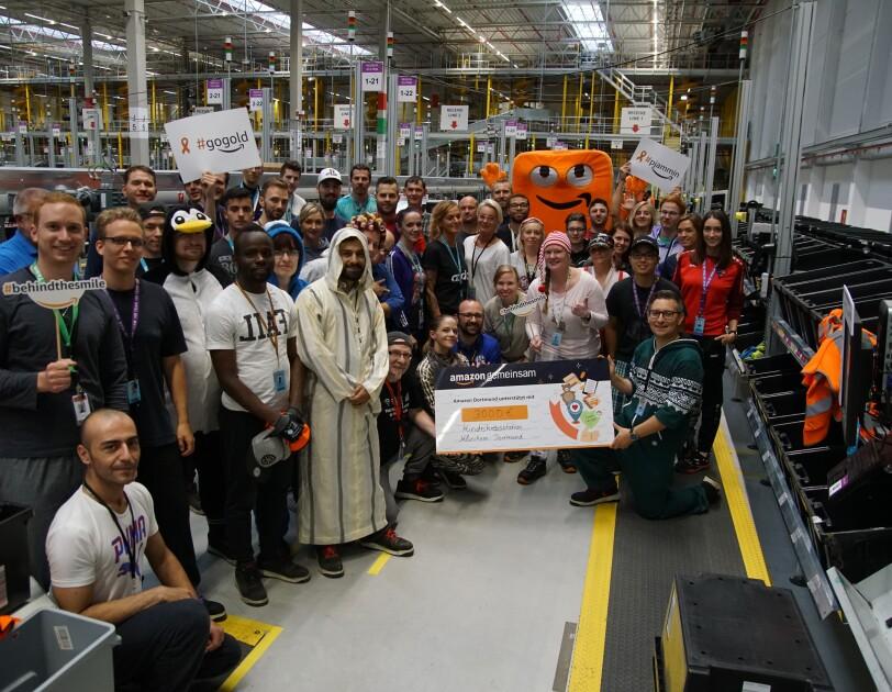 Rund 30 Mitarbeiter in Schlafanzügen haben sich in einer Logistikhalle fürs Gruppenbild versammelt. Alle gruppieren sich um einen großen Spendenscheck, der von einigen Mitarbeiter gehalten wird.