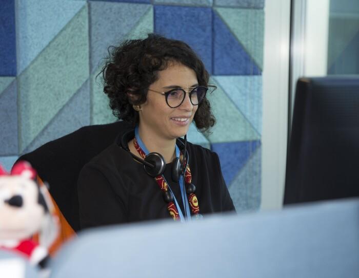 Sarah Beddini, Head of Vendor Management della sezione Giochi & Giocattoli di Amazon, siede alla sua scrivania, di fronte allo schermo del PC. In primo piano, fuori fuoco, un peluche del personaggio di Minnie.