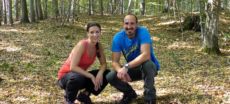 Ein Mann und eine Frau sitzen auf einem Waldboden und lachen in die Kamera.