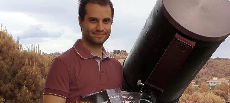 Ritratto di Daniele Gasparri. L'uomo regge in mano 3 libri di astronomia. Alla sua sinistra, un cannocchiale. Sullo sfondo, degli alberi.