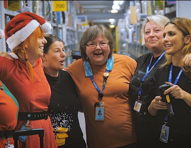 EineGruppe von 6 Mitarbeiterinnen steht in einem Regalgang. Eine trägt eine Weinachtszipfelmütze, ein andere ein Elfenkostüm.