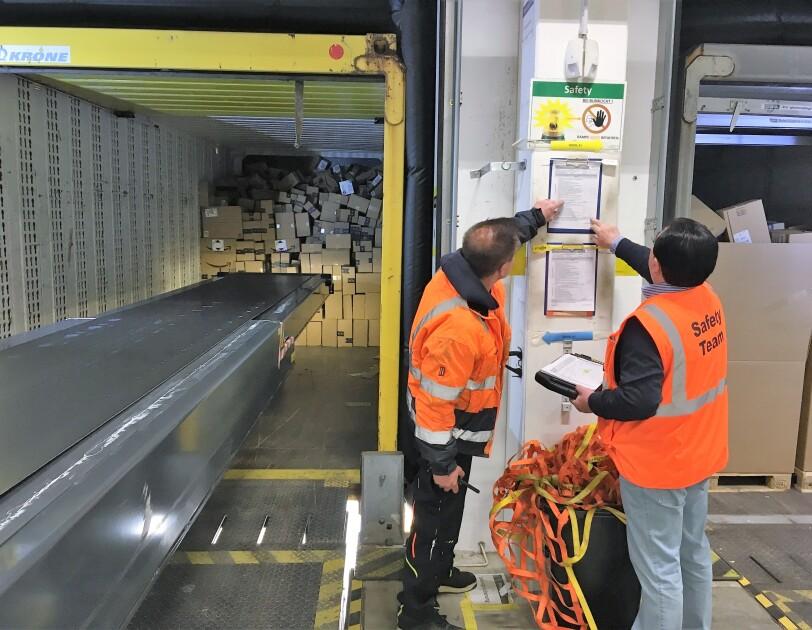 2 Männer in orange-farbenen Sicherheitswesten blicken auf ein Sicherheitsprotokoll. Rechts von ihnen sieht man das Innere einer Lkw-Brücke, in die ein Förderband für Pakete ragt.