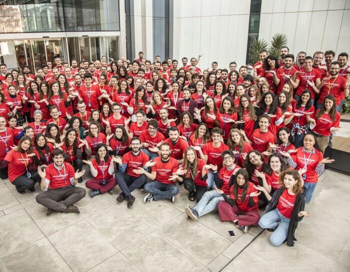 Gruppo di persone in posa con una t-shirt rossa ed entrambe le mani alzate a simulare una bilancia. Posano davanti all'ingresso di un ufficio Amazon.