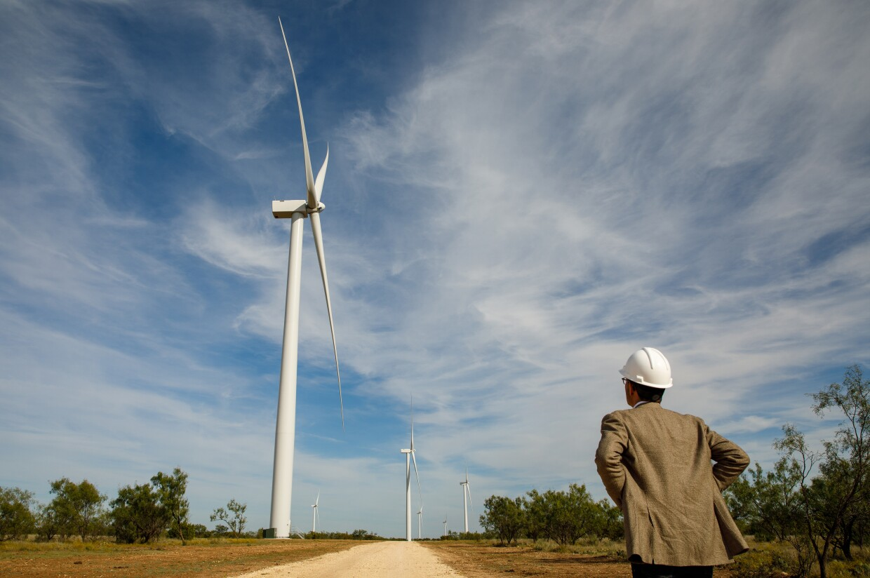 An employee with a hard hat faces a field of wind turbines, with blue sky and light clouds in the background.