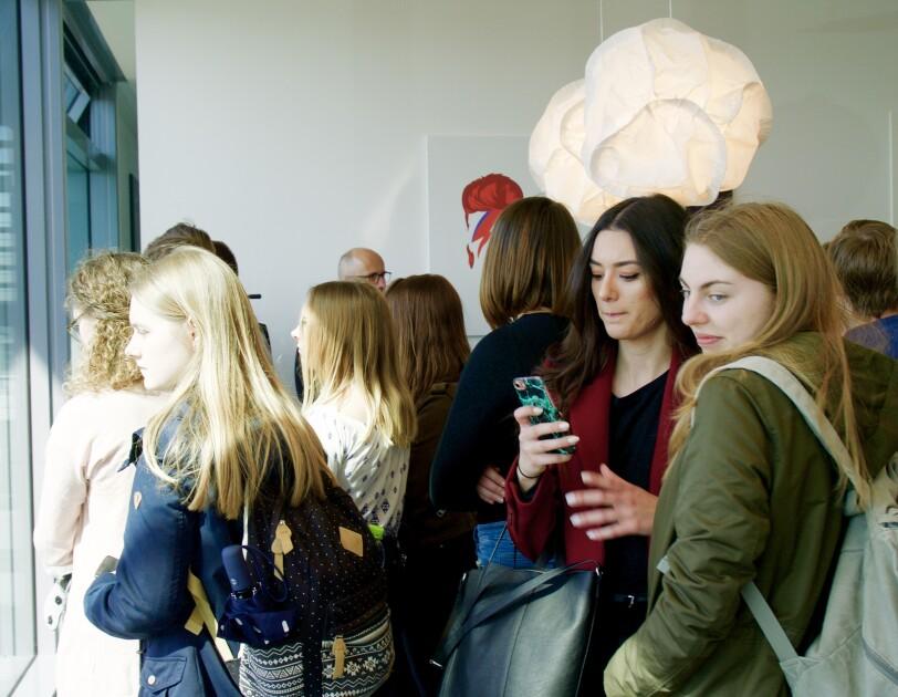 Eine Gruppe von Schülern drängt sich in einem Raum.
