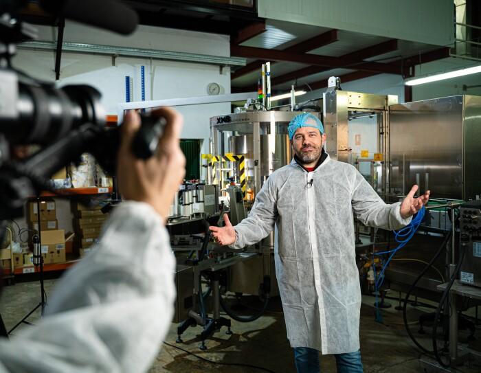 Juan Vicente Casanova, CEO de Espicy, en un momento de la grabación. Enfocado pero en segundo plano está Juan con una bata blanca y un gorro azul. En primer plano y desenfocado el brazo del cámara y la cámara. De fondo la fábrica donde se produce la salsa.