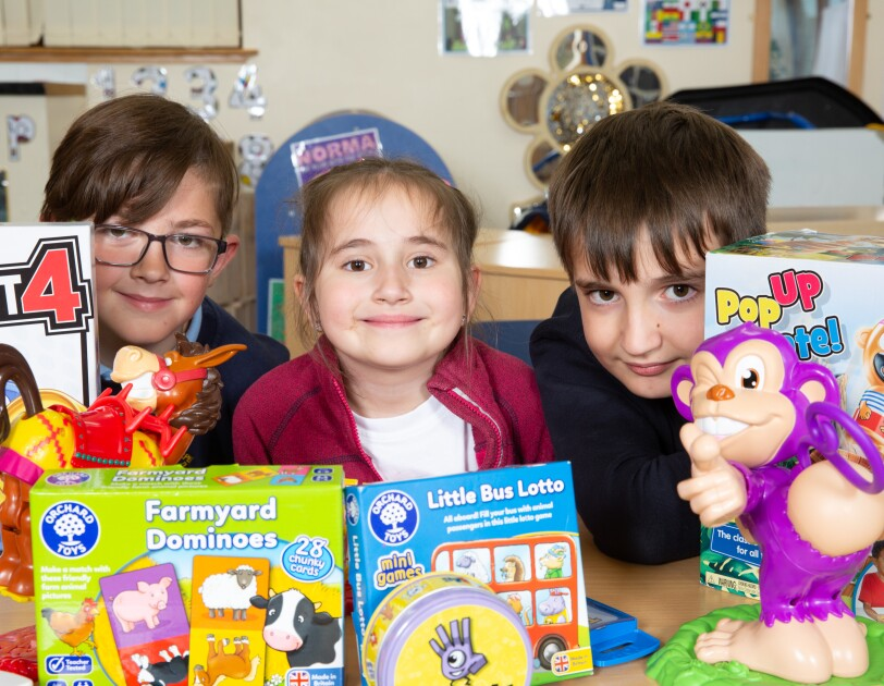 Three School children sitting behind a table full of colourful game boxes.