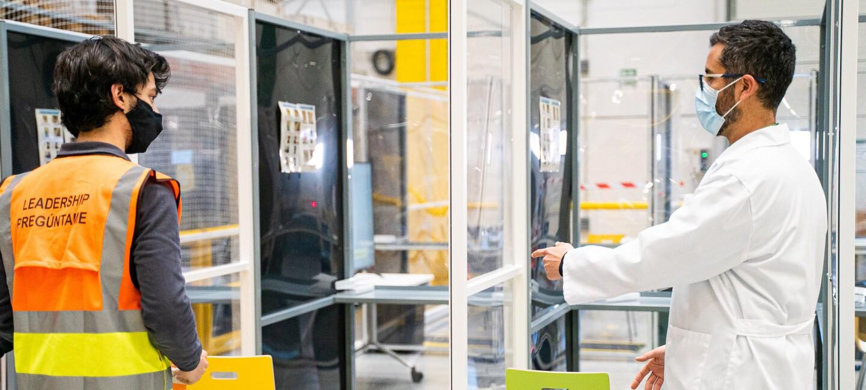 Gianluca Manuli dando indicaciones a un asociado antes de hacerse la PCR.  Hay tres puestos cubiertos con mamparas de plástico. El doctor Manuli va con una bata de médico blanca y lleva mascarilla y gafas negras. Da instrucciones a un asociado que va con un chaleco amarillo y naranja, tejanos y mascarilla negra.