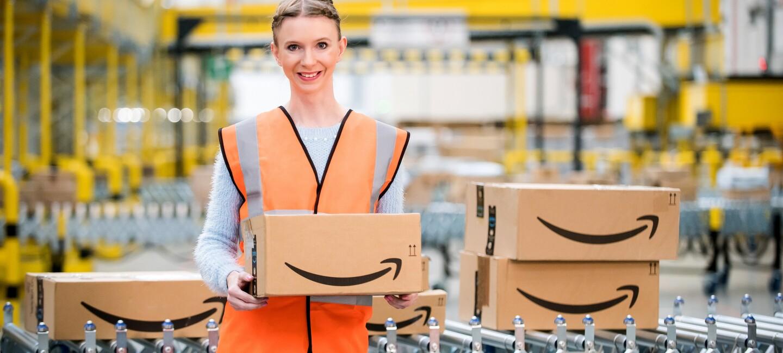 Uśmiechnięta pracowniczka Amazon trzymająca zapakowane zamówienie, w tle centrum logistyki.