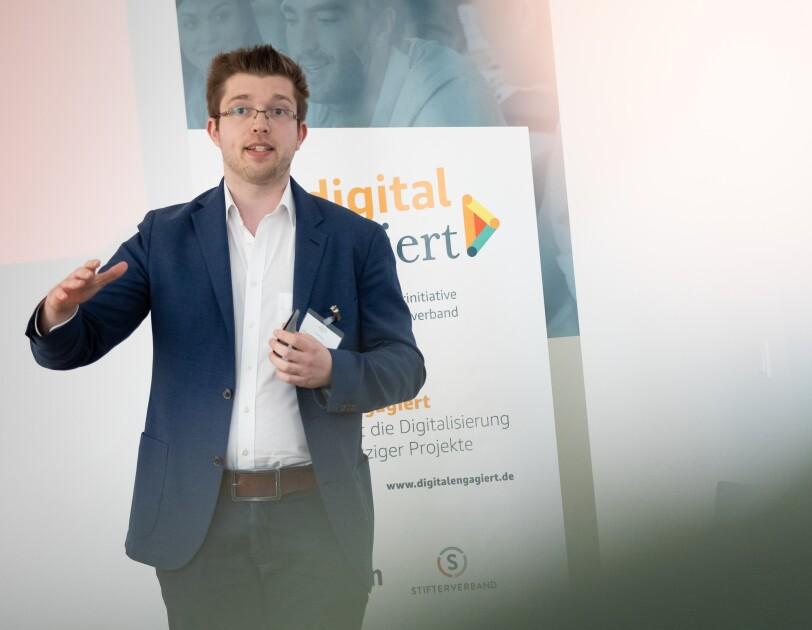 Daniel Stark steht vor einem digital.engagiert-Poster und gestikuliert