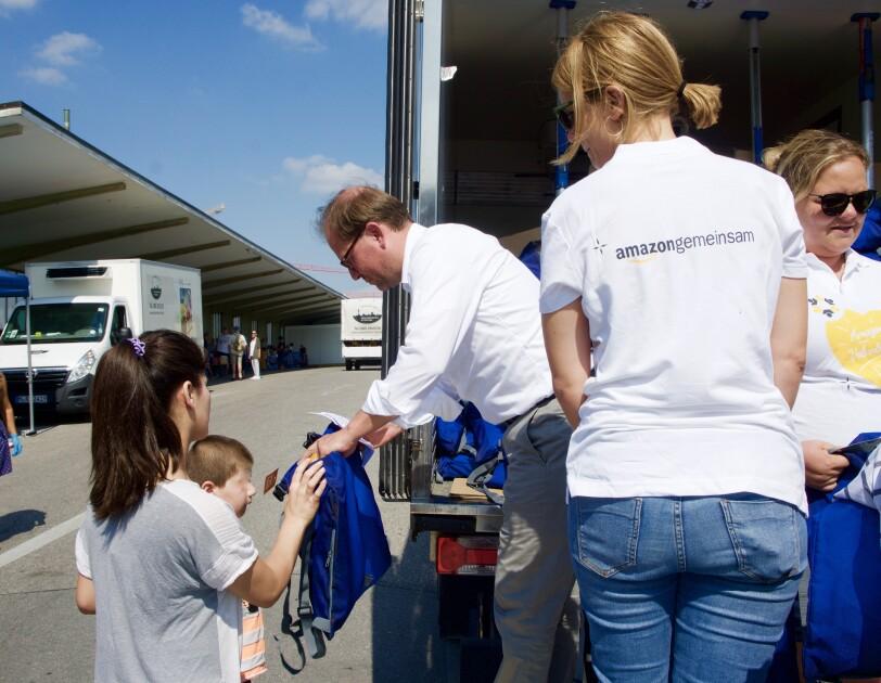 Helfer verteilen vor einem Lkw blaue Schulbeutel.