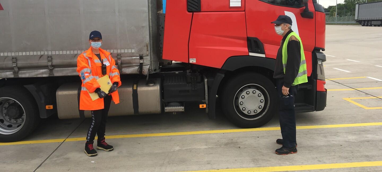 Eine Frau in orangener Sicherheitsjacke mit Mundschutz und ein Truckerfahrer (ebenfalls mit Mundschutz) in gelber Sicherheitsweste stehen in ca. 2 m Abstand vor einem roten Trucker.