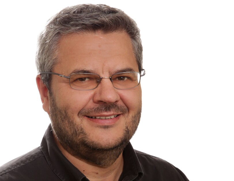 Daniel Marcu, director of machine translation and natural-language processing at Amazon. He is wearing a brown shirt and has glasses and a beard.
