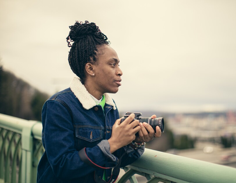 A woman in a blue jacket and green top, and holding a camera, looks to the right from atop a bridge.