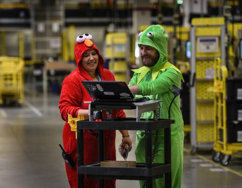 2 Mitarbeiter in Kostümen im Logistikzentrum.