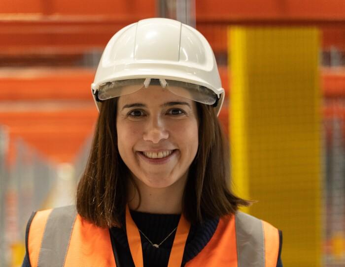 Isabel Bermúdez, Responsable Senior de Proyectos de Ingeniería para Amazon España, mirando a cámara y sonriendo. Lleva casco blanco, chaleco naranja. Tiene el pelo por el hombro. El fondo está difuminado.