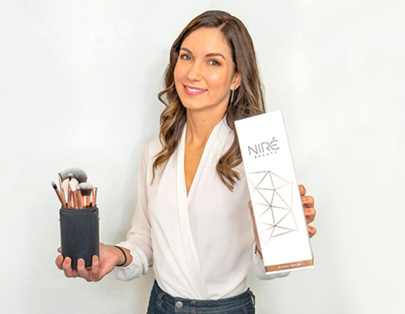 Owner of NIREBAUT Erin, holding up make-up brushes