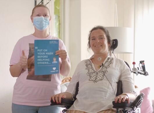 Eine Pflegekraft neben einer jungen Frau im Rollstuhl