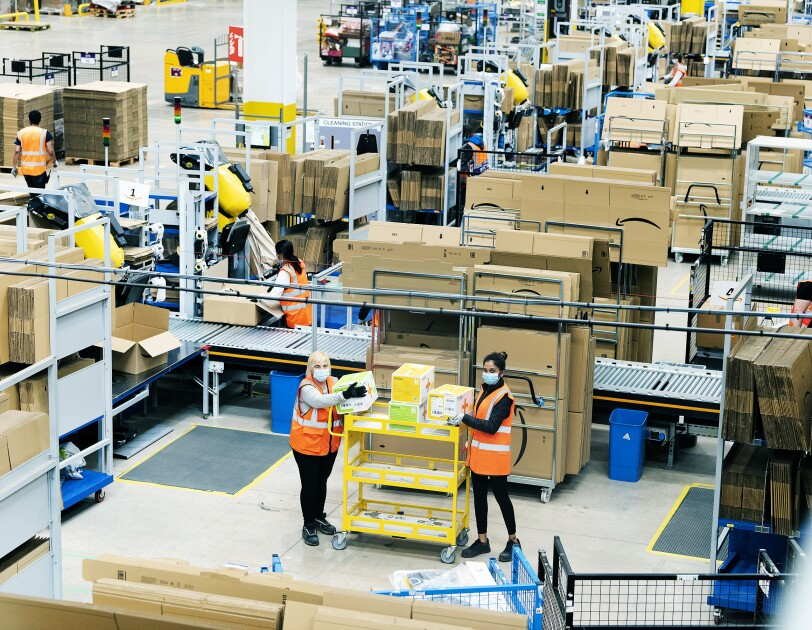 Wide shot of Amazon fulfilment centre staff stacking a yellow cart with medical supplies in the Coalville Fulfilment centre to provide supplies to the relevant government centres. They are wearing protective gloves and face masks while maintaining a social distance.