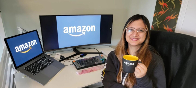 InternDay. Una mujer de unos 25 años con el pelo largo de color negro y mechas de color marrón. Lleva una sudadera de Amazon y está agarrando con la mano izquierda una taza de color negro por fuera y amarilla por dentro con el logo de Amazon en color blanco. Está sentada en una silla delante de su mesa y dándole la espalda. En la mesa hay un ordenador portátil conectado a un display port y tiene una pantalla muy grande y un teclado. En las dos pantallas aparece el logo de Amazon. En la parte izquierda hay una barandilla de hierro blanca y en la derecha un cuadro rectangular vertical con un estampado de hojas de color rojo, naranja y verde.
