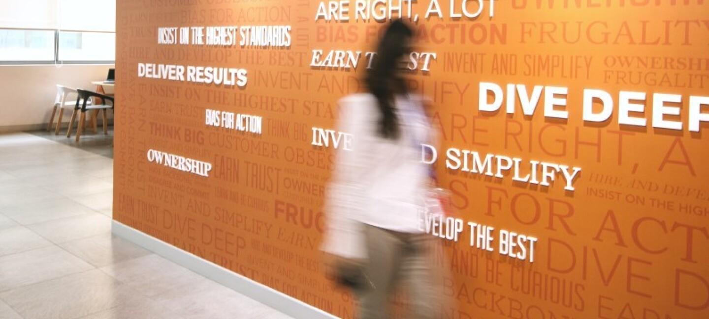 Una trabajadora de Amazon está caminando po la oficina, se ve movida su figura pero tiene el pelo largo negro, lleva una camisa blanca de manga langa y unos pantalones de color beige. En la mano parece uqe lleva el teléfono. Está pasando por delante de un pared con los Principios de lideerazgos escritos en color blanco siendo la pared de color naranja.