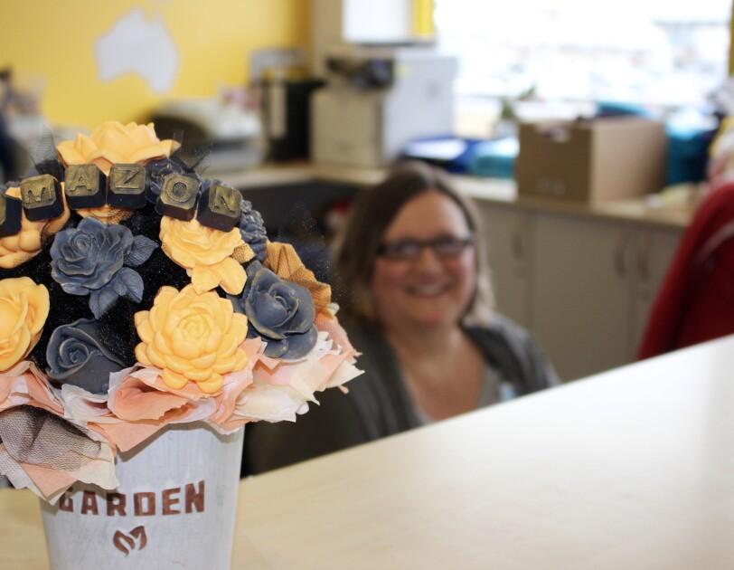 """Auf dem Empfangsdesk des Logistikzentrums steht ein bunter Strauß an Seifenblumen, in deren Mitte steht """"Amazon""""."""