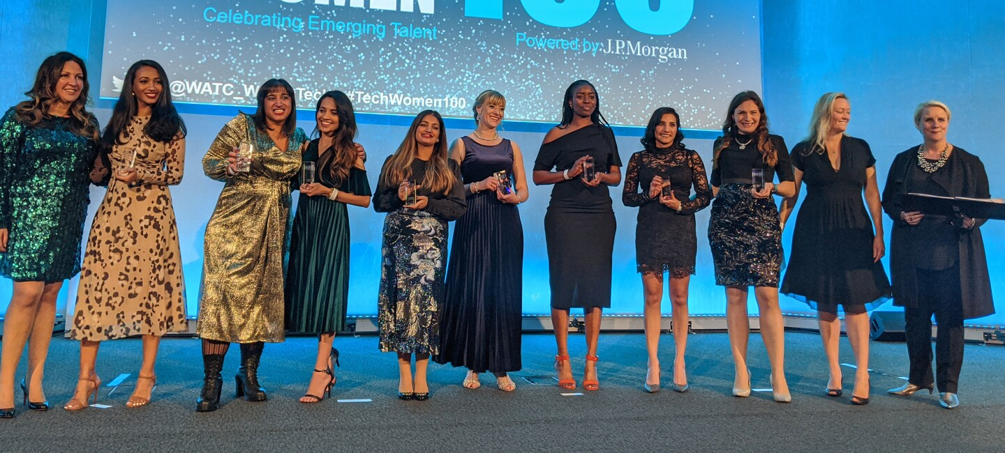 Women in tech award winners on stage with their awards. They are standing in front of a projection reading TechWomen100
