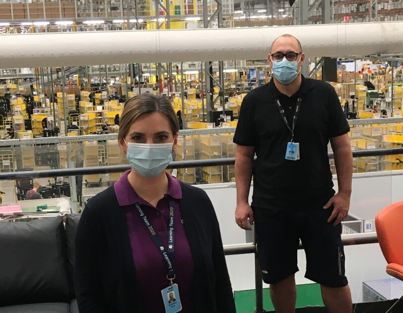 Married couple Marian Popescu and Andreea Cristina Neagu, who both work at Amazon's fulfilment centre in Peterborough, pictured with the shop-floor in the background.