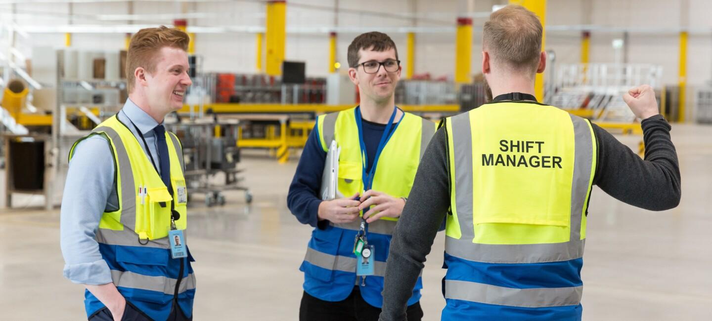 Drei Männer in gelb-blauen Warnwesten unterhalten sich miteinander. Im Hintergrund ist der Innenraum eines Verteilzentrums zu sehen.