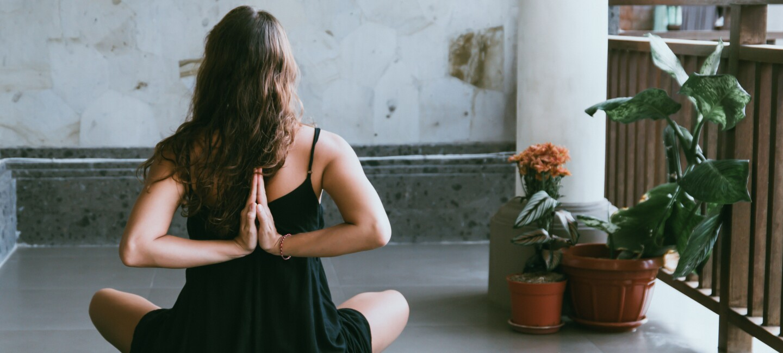 Eine Frau sitzt im Schneidersitz und macht Yoga