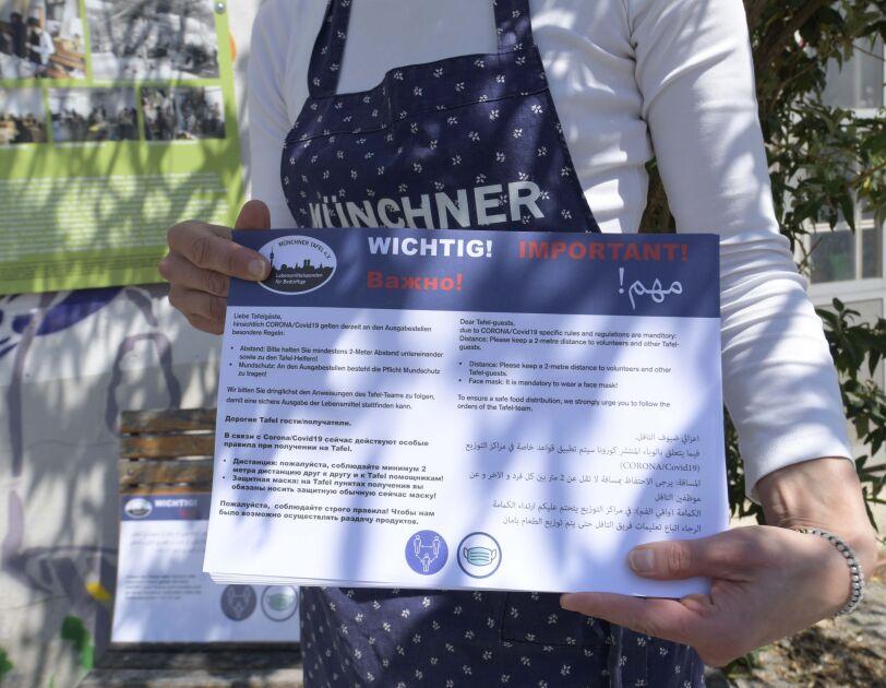 Mitarbeiterin der Münchner TAfel mit einem Informationshinweis.