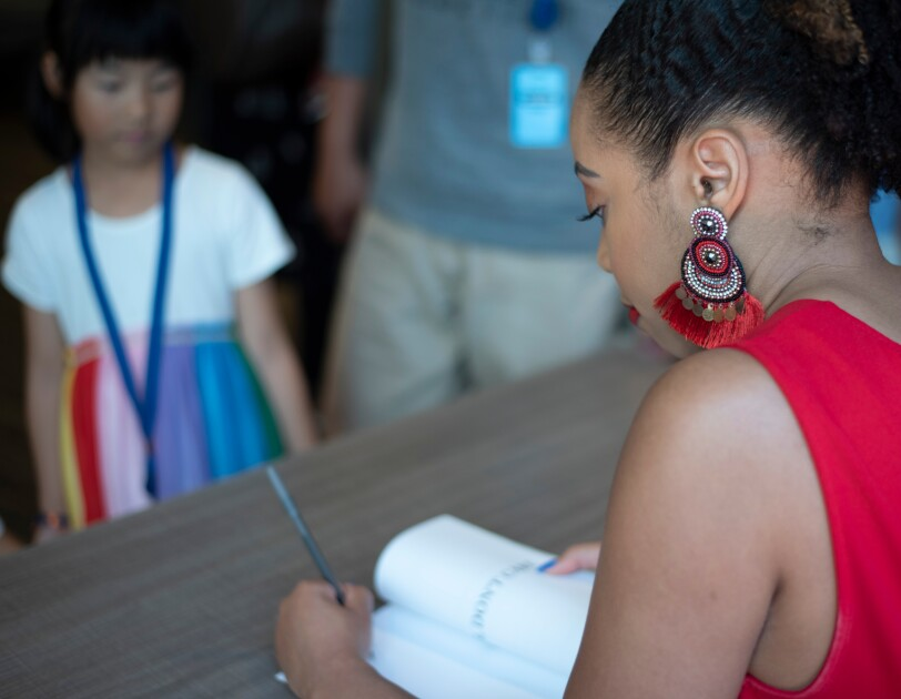 A girl looks on while a woman in a red dress writes in a book.