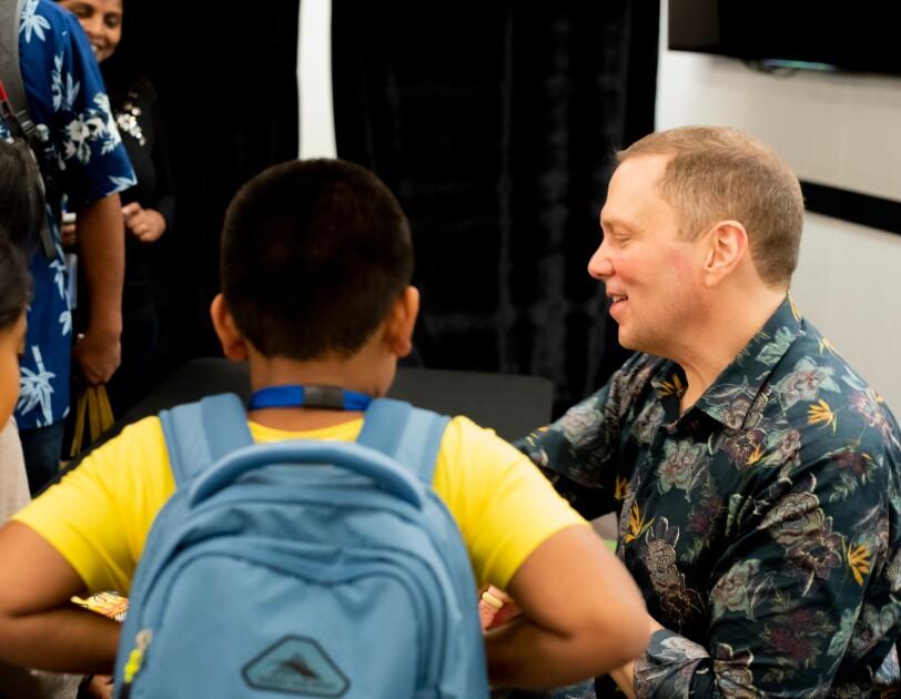 Several children gather around a man.