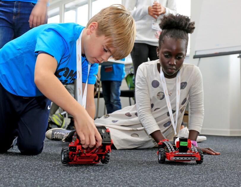 Ein blonder Junge und ein dunkelhäutiges Mädchen knien auf dem Boden und blicken auf zwei rote Modell-Transportroboter .