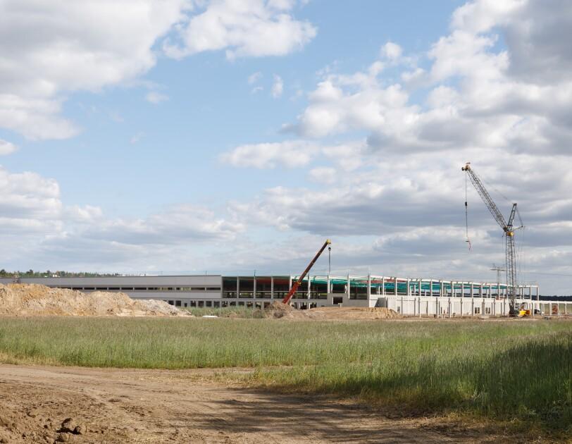 Ein flaches, großes Gebäude im Rohbau, Kräne sind zu sehen.