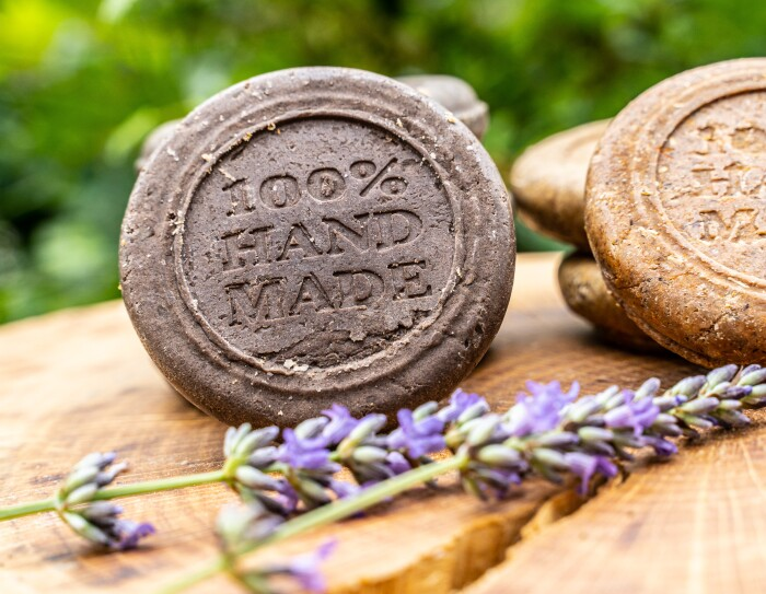 La cosmética de María ofrece dieciocho productos.  En la foto hay dos jabones sólidos, con  una ramita de lavanda y encima de un tronco. Los jabones son de color redondo y tienen grabado lo siguiente: 100% handmade.