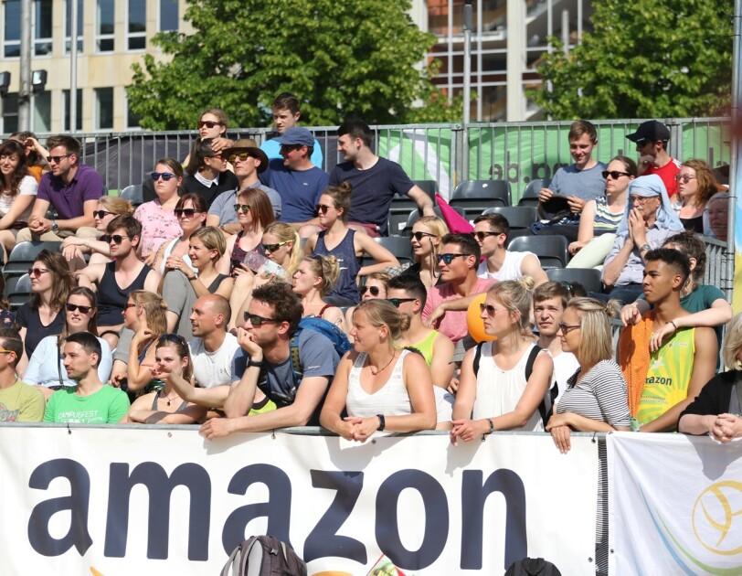 Hiner einem Amazon Banner am Spielfeld sind eine Reihe von Zuschauern