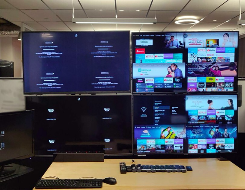 4 monitors in a work space, with a row of remotes and keyboard in front of them.
