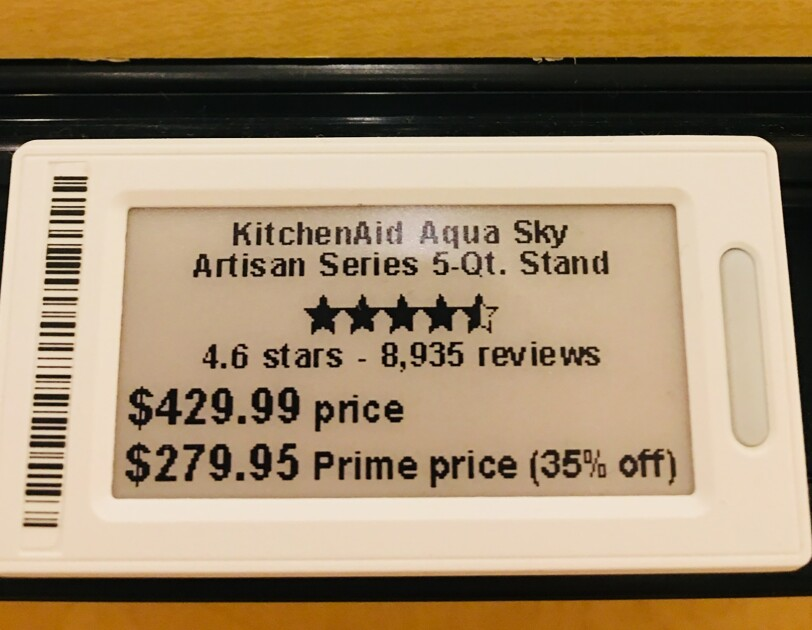 A digital tag for a KitchenAid Artisan Series 5-Qt. stand mixer in aqua sky. The tag shows that the mixer has 4.6 stars and 8,935 reviews at the time the photograph was taken. The regular price is $429.99, with a Prime member price of $279.95 (35 percent off). Behind the tag is an aqua blue KitchenAid stand mixer with stainless bowl.