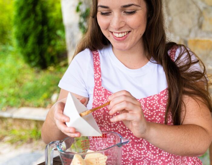 Alejandra Gómez Iribarnegaray tiene pelo largo y castaño. Lleva una camiseta de color blanco y encima un vestido de algodón con tirantes por encima de color blanco y rosa.