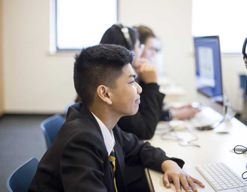 A school boy from Uxbridge siting at a computer in an IT lesson.