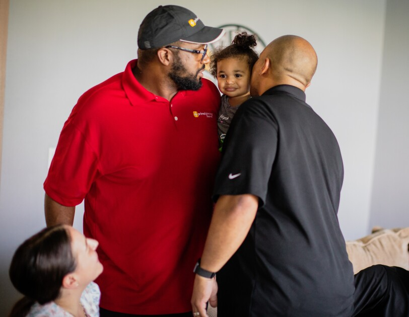 At a family gathering, a young child is hugged by two adults.